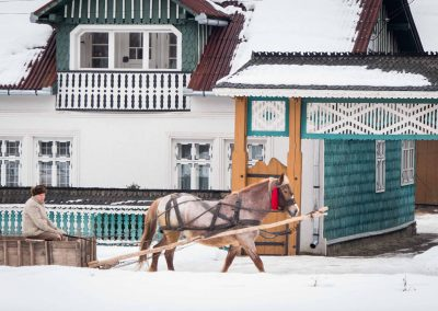 Riding a sleigh in a village in Maramures